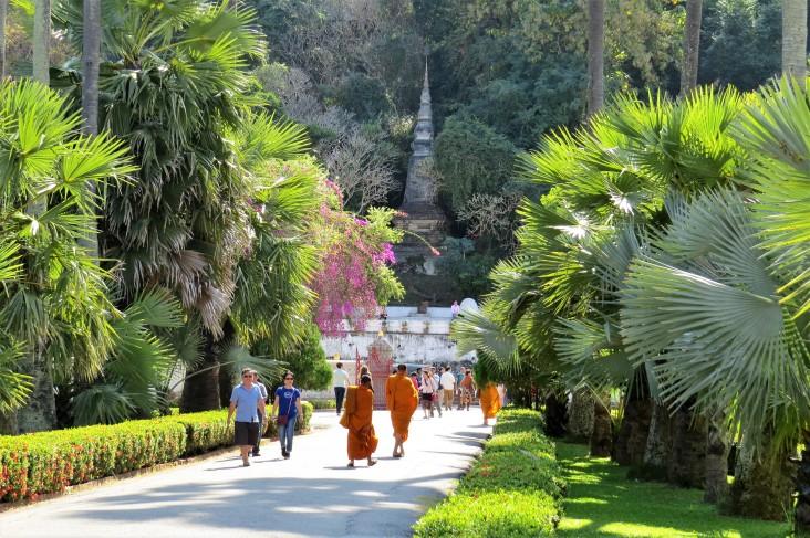 Monges e turistas caminhando pelos jardins do complexo