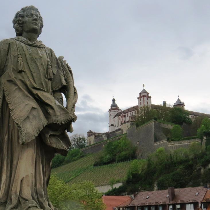 Uma das 12 estátuas da que adornam a ponte Alte Mainbrücke. Ao fundo, a fortaleza Festung Marienberg e vinhedos