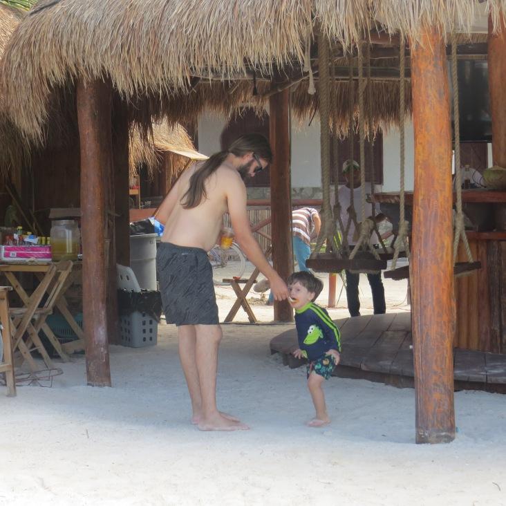 Tales comendo manga com o papai em quiosque de praia em Holbox